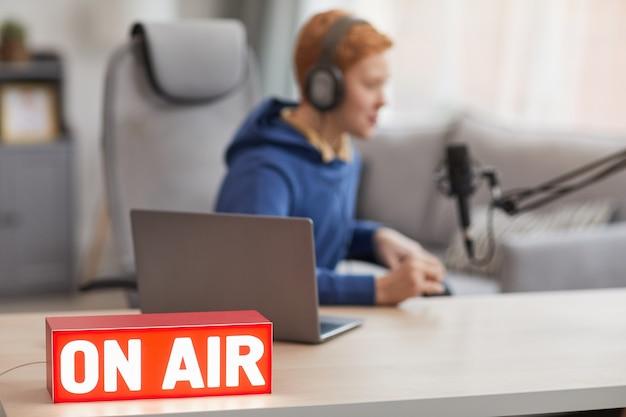 オンラインストリーミング中にマイクに向かって話している10代の少年のぼやけた形の赤いonairサインの背景画像、コピースペース