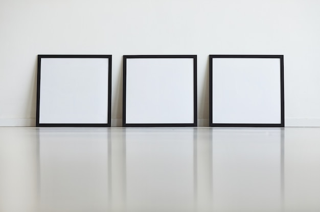 Background image of three identical black frames set against white wall in row at art gallery,