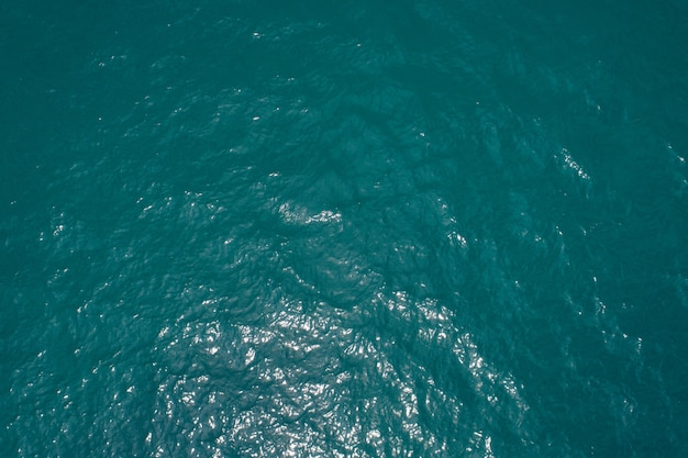 Background image of the tropical sea surface water smooth surface ocean reflection of sun top view by drone camera.