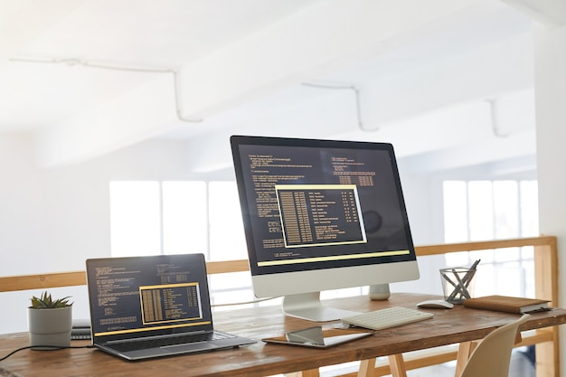 Background image of two computers with programming code on screen in minimal home office interior with wooden accents, copy space