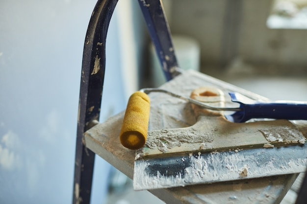 Background image of used spatula and paint roller lying on top of ladder on construction site or in house building, copy space