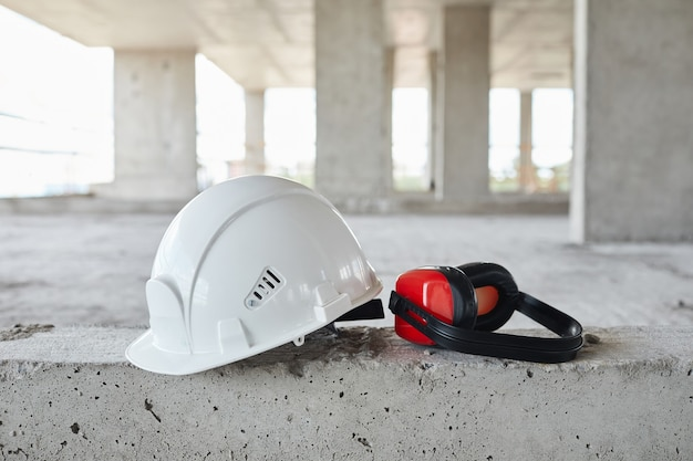 Background image of white hardhat and tools on floor at construction site copy space