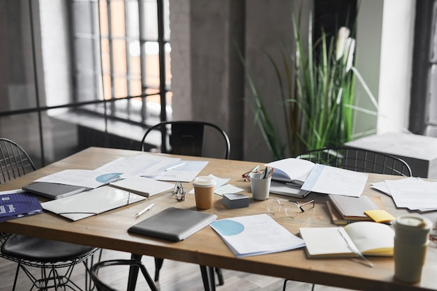 Background image of wooden table with documents scattered on after business meeting in office, copy space