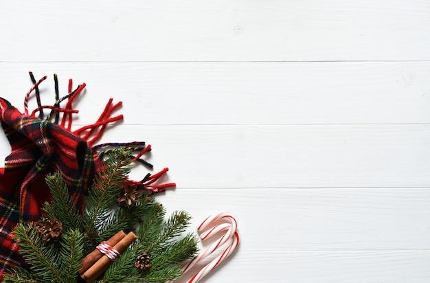 크리스마스 컨셉의 배경입니다. 전나무, 스카프 및 사탕 지팡이로 장식