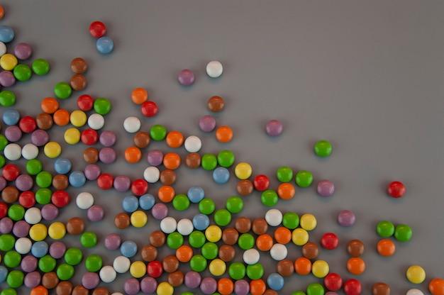 회색 배경에 뿌린 색 사탕 형태의 배경