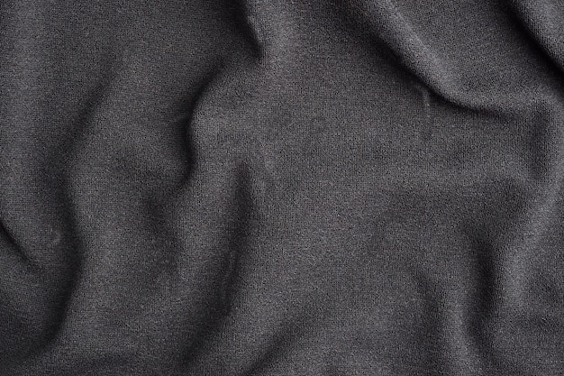 Background is made of black textile material, the texture of a piece of clothing.