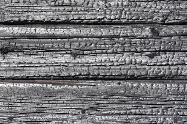 Background is texture of burnt wooden house wall logs