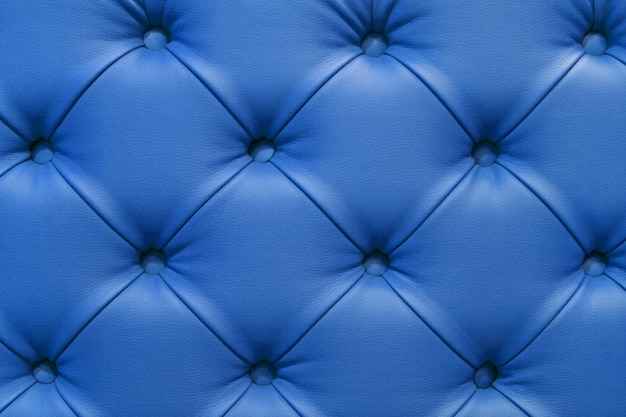 Background of leather blue sofa, stitched buttons.