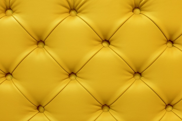 Background of leather yellow sofa, stitched buttons.