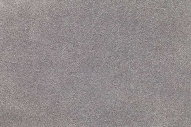 Background of light gray suede fabric closeup. velvet matt texture of silver nubuck textile