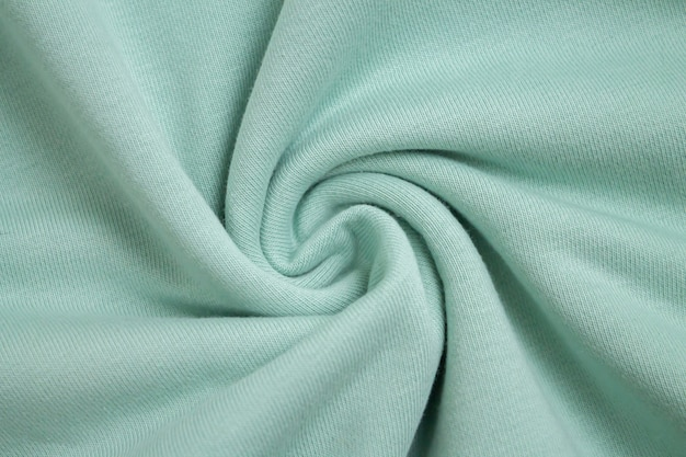 Background of light green fabric sample from above view