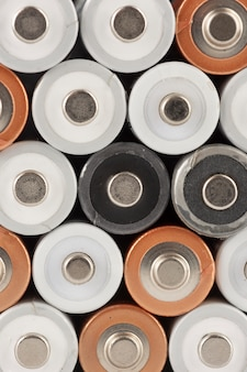 Background made of pile of old white, black and golden aa batteries showing positive end