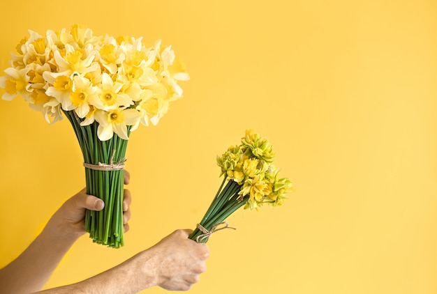 Background male hands with a bouquet of flowers.