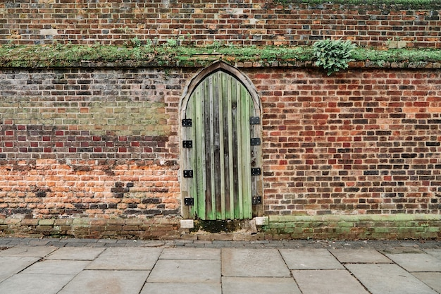 Background of a medieval door on a weathered stony wall.