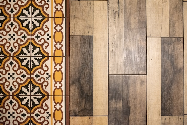 Background of mediterranean retro colors tiles next to wooden floor.