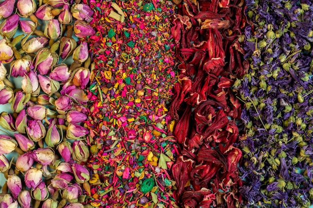 Background of mixed herbal tea blooms rose petals dried rose buds and herbs top view