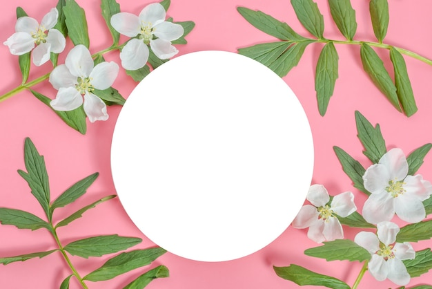 Background mock up greeting card, place for an inscription in the form of a white circle with a frame of flowers and leaves on a pink background