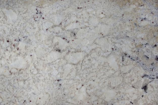 화강암 bianco romano라는 어두운 얼룩이있는 배경 자연석 베이지.