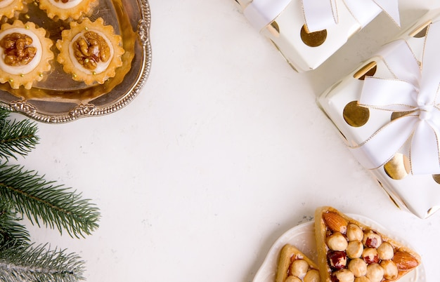 Background for new year or christmas. cookies, christmas tree, gifts on a white table