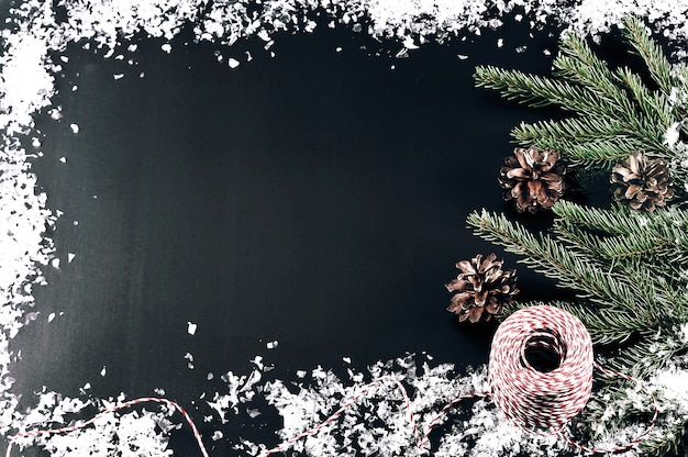 Background for new year greetings with tree branches, cones and snow