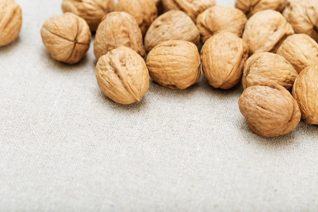 Background of nuts on light textile surface with copy space.