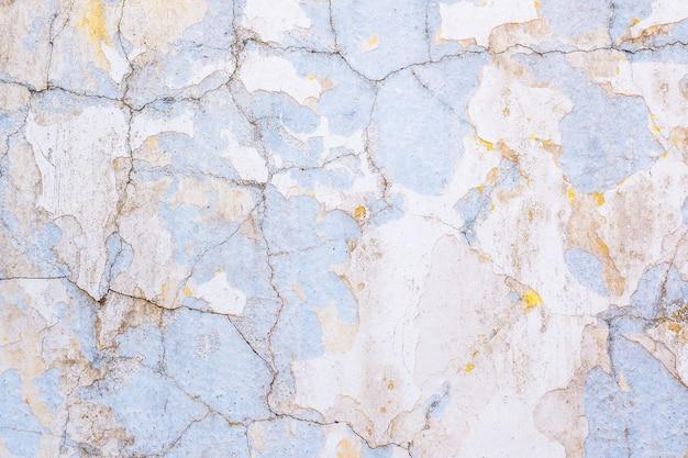 古い白塗りの背景は、黄色と青の無垢の壁に塗装が剥がれ、ひびが入っています。