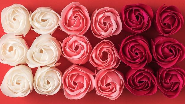 세 가지 색상의 인공 장미 꽃 봉오리의 배경. 꽃 배경입니다.