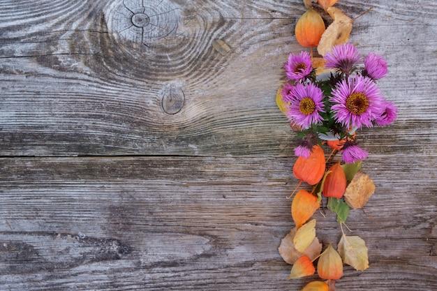 가을 꽃, 국화, physalis, 오래 된 나무 보드에 노란 잎의 배경