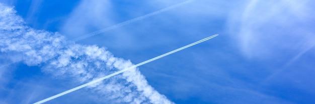 白い雲と飛行機からのトレイルと美しい明るい青い日の空の背景。バナー Premium写真