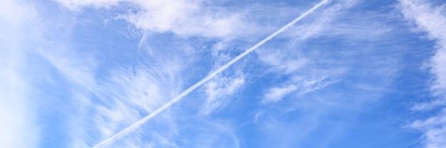 白い雲と飛行機からのトレイルと美しい明るい青い日の空の背景。バナー