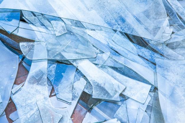 青い色調の床の割れたガラスの背景。