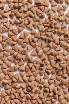 猫乾燥食品の背景。ミニマルな白いフラット。