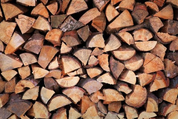 刻んだ薪の背景が山積みになっています。冬に向けて用意された薪のみじん切りの山。古い薪の山の背景