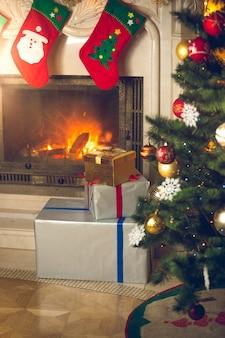 贈り物のための伝統的なストッキングで飾られた燃える暖炉のあるリビングルームのクリスマスツリーの背景
