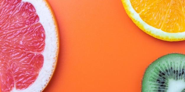柑橘系の果物、オレンジスライス、キウイ、グレープフルーツの背景。