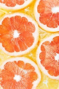 柑橘系の果物のオレンジとグレープフルーツのスライスの背景。ストゥディ