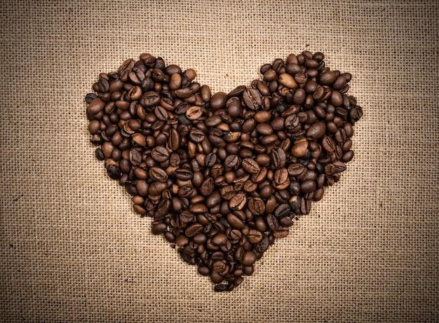 Фон кофейных зерен в форме сердца на фоне мешковины
