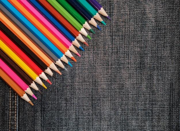 縫い目が付いているデニム生地の色鉛筆の背景