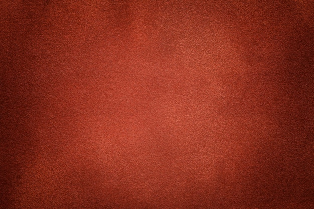 Предпосылка темного оранжевого крупного плана ткани замши. бархатная матовая текстура имбиря, нубука, текстиля