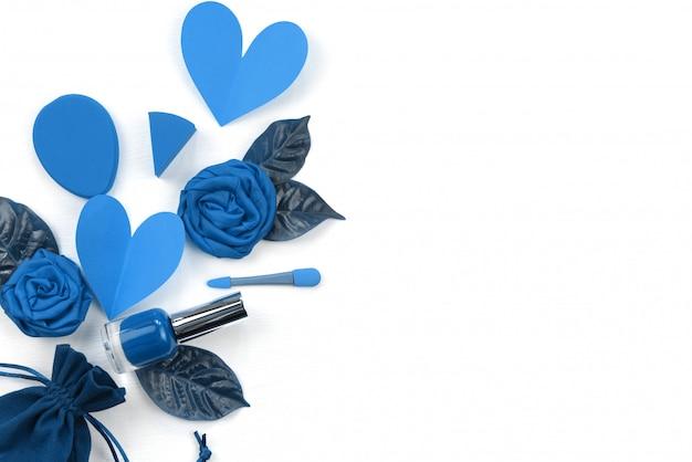白地に青で装飾的な化粧品の背景。バレンタインデーの組成の概念はフラット横になっている口紅花心葉マニキュア