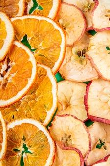 Фон из сухофруктов яблоко и апельсиновые дольки вид сверху
