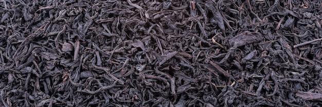 乾燥茶の背景は濃い色の葉です。マクロ