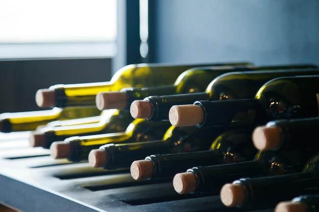 ラックの家の居心地の良いキッチンエリアのインテリアにまっすぐな列の空と満たされたワインボトルの背景。デザインのためのキッチン静物。家の快適さとリラクゼーションの概念。コピースペース