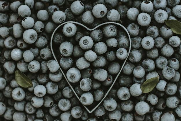 Фон из свежих замороженных ягод черники с металлической формой сердца. текстура черники крупным планом. летний урожай ягод. место для текста