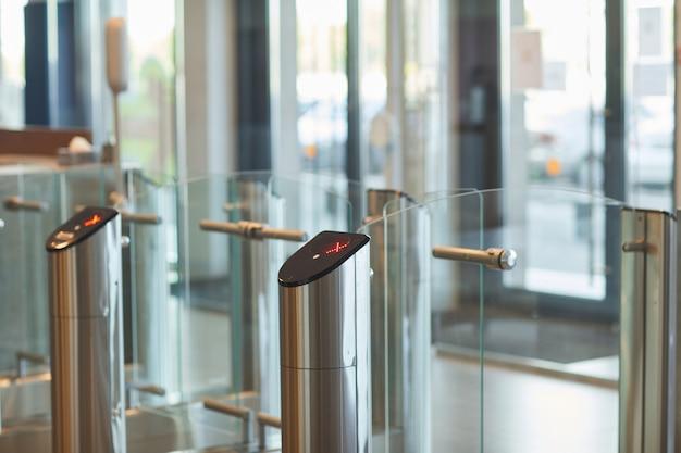 사무실 건물 또는 대학 입구에 자동 게이트가있는 유리 문의 배경, 복사 공간