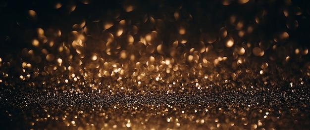 金と黒のキラキラライトの背景焦点がぼけた抽象的な背景