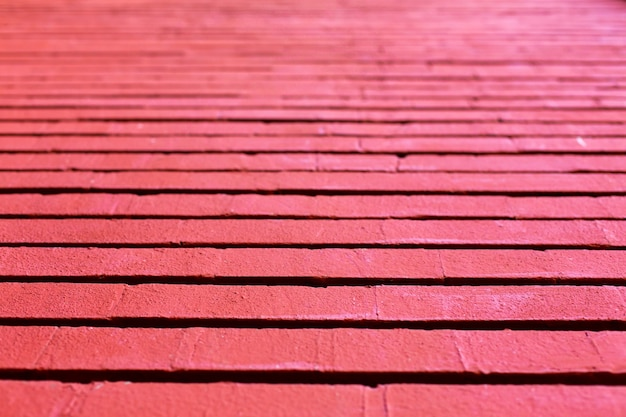 色あせた赤で描かれた木の板の横縞の背景。