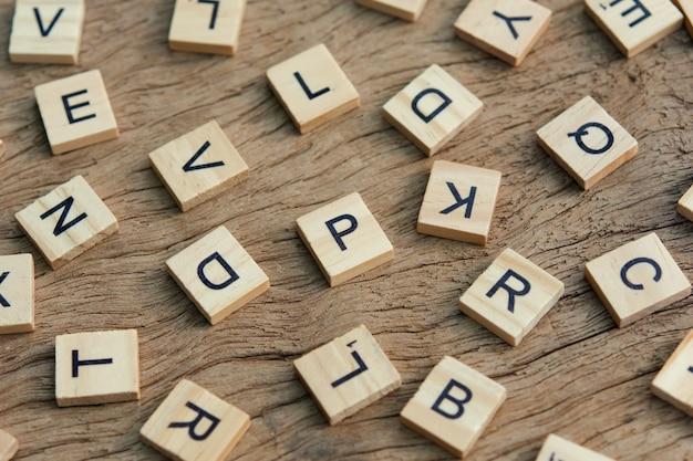 木製の背景に活版印刷の木版印刷ブロックの背景、アルファベットのランダムな文字と黒インクで染色された句読点