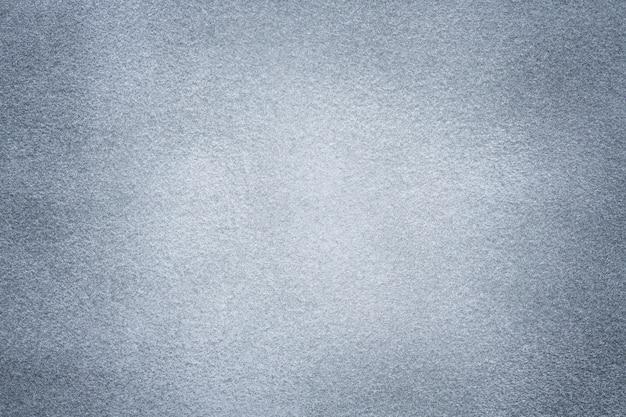 Фон из светло-серой замшевой ткани крупным планом бархатная матовая текстура из серебристого нубука с текстилем