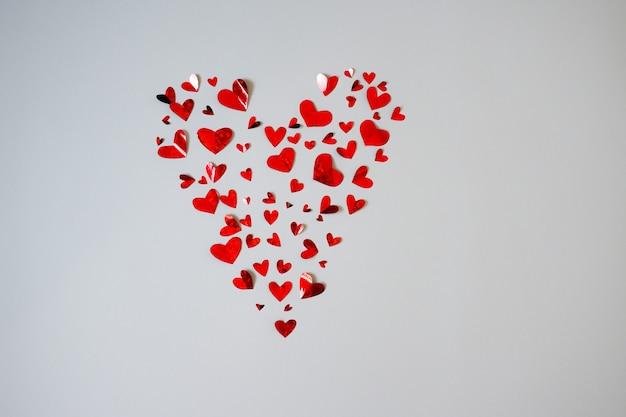 Фон из многих красных маленьких сердец, образующих одно большое сердце, изолированные на белом фоне